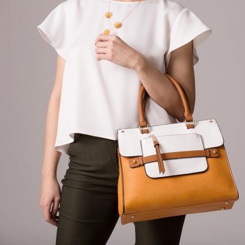 Stylish woman in modern clothes with bright orange white handbag in hands posing at studio isolated on gray background