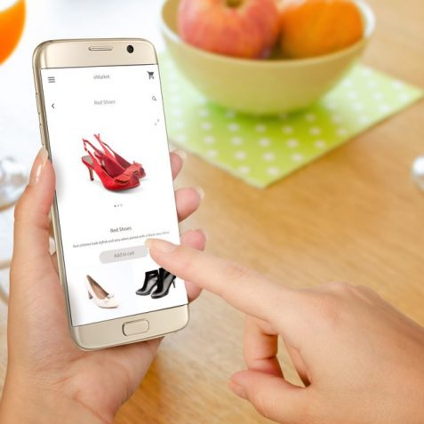 Online shopping with smart phone. Isolated phone in woman hand. Buying women shoes on online store.
